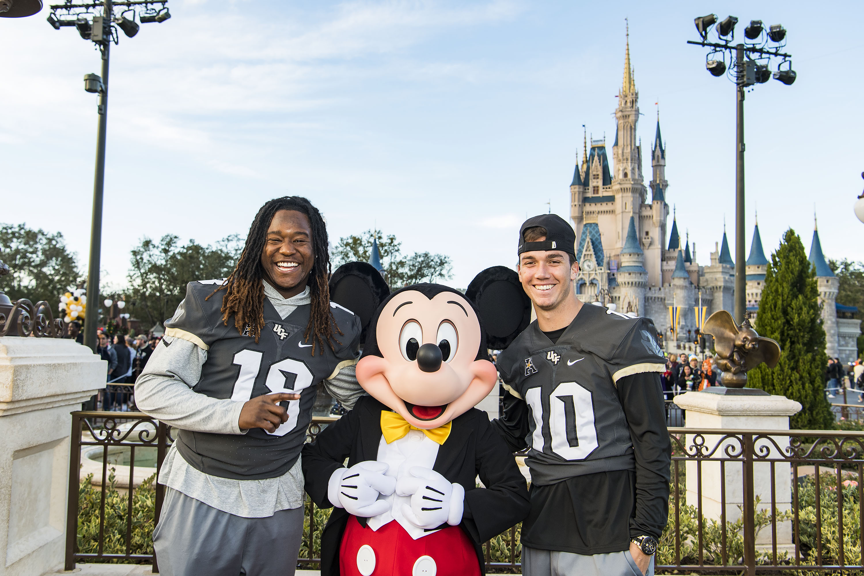 The University of Central Florida Knights linebacker Shaquem Griffin and quarterback McKenzie Milton pose with Mickey Mouse