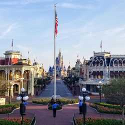 Security Cast Members raise the flag at a closed Magic Kingdom due to COVID-19