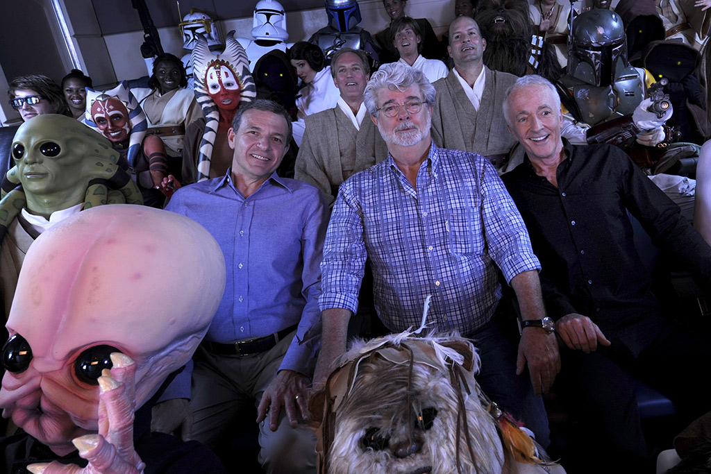 "Walt Disney Co. president and CEO Bob Iger (left) ""Star Wars"" creator George Lucas (center) and actor Anthony Daniels, who portrayed C-3PO in ""Star Wars"" (right), pose with ""Star Wars"" characters May 20, 2011 inside a ""Star Tours"" ride vehicle at Disney's Hollywood Studios"