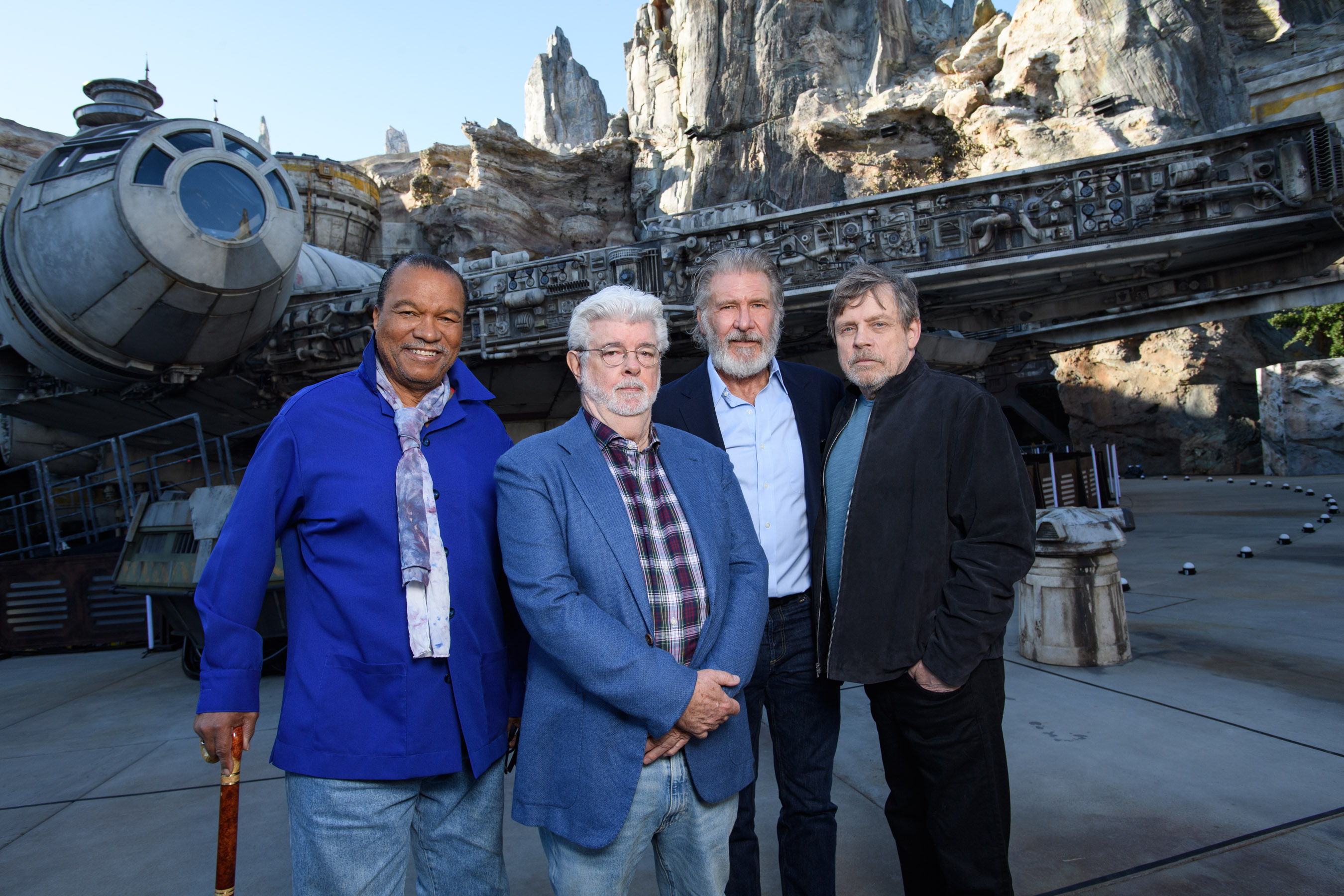 Actor Billy Dee Williams, Star Wars creator George Lucas, actors Harrison Ford and Mark Hamill pose in front of the Millennium Falcon at Star Wars: Galaxy's Edge at Disneyland