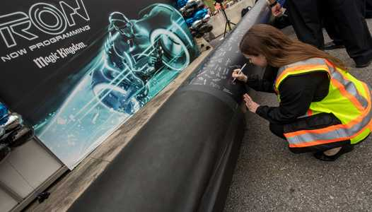 PHOTO - Magic Kingdom cast members sign one of the first steel support columns for the upcoming TRON coaster