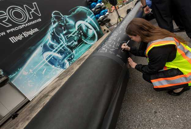 Cast Members sign steel support column for TRON