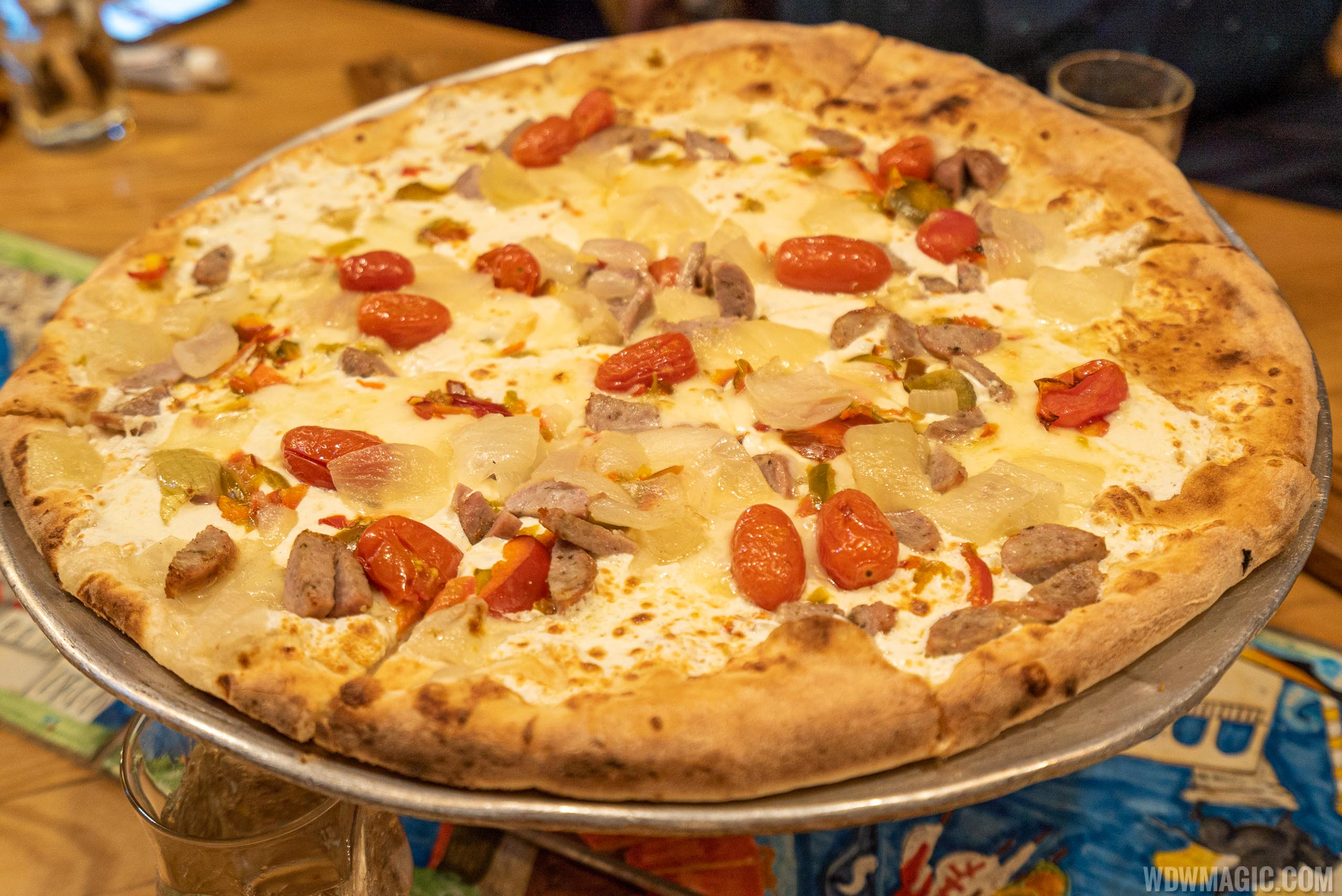 Via Napoli San Gennaro Pizza - Mozzarella, fontina, sweet Italian sausage, cherry peppers, onions, tomato